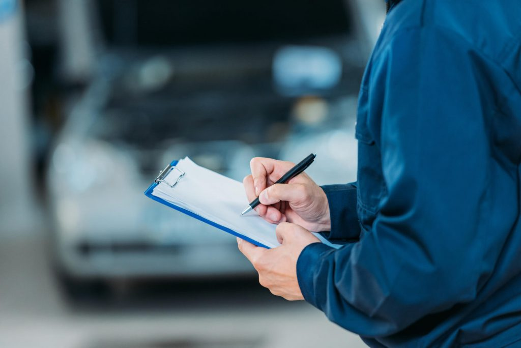 a mechanic is writing on a notepad