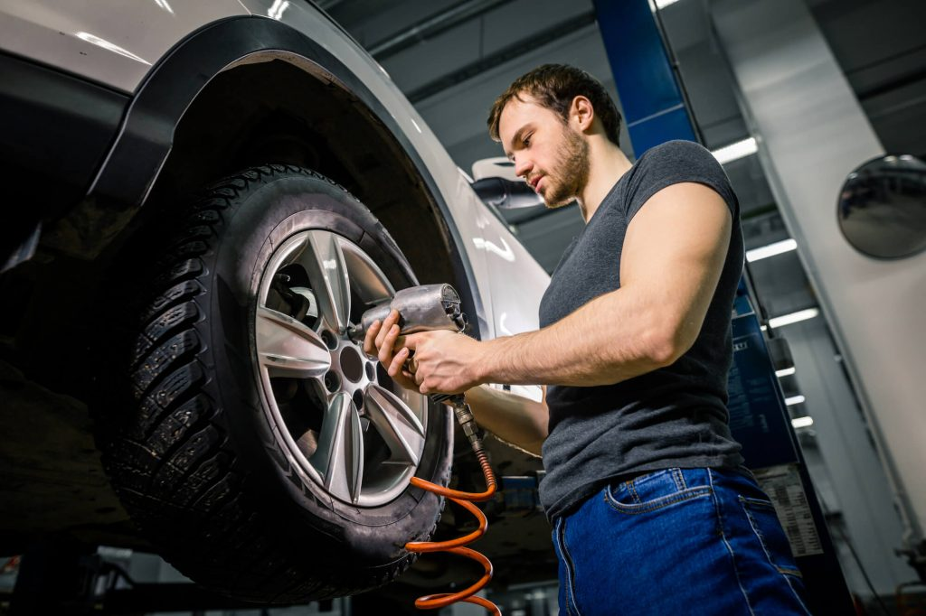 A young mechanic is fitting a tyre