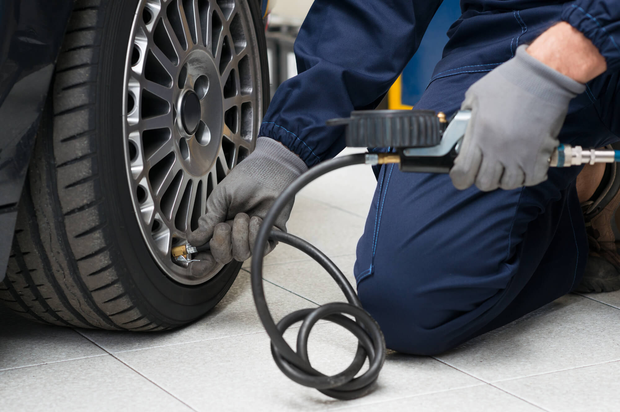 a mechanic is checking the air in the tyre