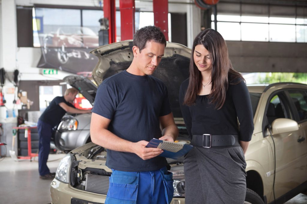 a car repairs garage owner is talking to a female customer